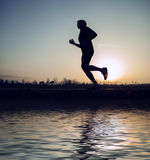 Runner sunset silhouette with mirror in water Stock Photos