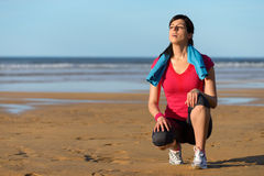 Runner sweating and taking a break. Tired sweaty runner taking a break after running and exercising on the beach. Sweaty woman resting and breathing after hard Royalty Free Stock Photo