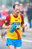 Runner take refreshing water shower in ASICS Stockholm Marathon Royalty Free Stock Photography