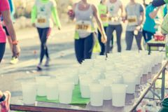 Runner taking a cup of water at H20 stand. Royalty Free Stock Photography