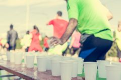 Runner taking a cup of water at H20 stand. Royalty Free Stock Images