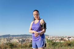 Runner taking pulse. Sportswoman is taking pulse at the city park Royalty Free Stock Photos