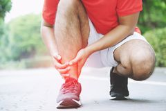 Runner touching painful twisted or broken ankle. Athlete runner training accident. stock images