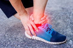 Runner touching painful twisted or broken ankle. Athlete runner training accident. Sport running ankle sprain.  Stock Photos