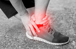 Runner touching painful twisted or broken ankle Royalty Free Stock Images