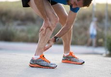 Runner touching painful twisted or broken ankle. royalty free stock image