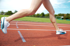 Runner on Track. A female athlete running on a track in summer Royalty Free Stock Photography