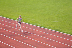 Runner on Track. A female athlete running on a track in summer Stock Image