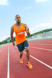 Runner At the Track. African American man in his 30s running at a sports track outdoors Royalty Free Stock Images
