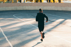 Runner on track at sport stadium, free space. Back of professional sportsman, training on open-air sports field. Fitness, workout, healthy lifestyle concept Royalty Free Stock Photos