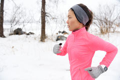 Runner trail running in cold winter snow. Female runner trail running in cold snowing weather. Asian Chinese athlete woman training for marathon jogging outside Royalty Free Stock Photo