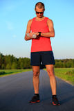 Runner training and checking stopwatch smart watch, cross countr Royalty Free Stock Photography