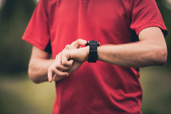 Runner training and using stopwatch with heart rate monitor Royalty Free Stock Image