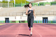 Runner trainning at a racetrack. Full length of beautiful young woman running along the racetrack stock images