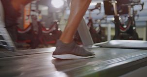 Runner on treadmill. Close up low section of a young mixed race man running on a treadmill stock video footage
