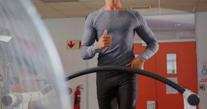 Runner on treadmill. Front view of a young mixed race man running on a treadmill stock video