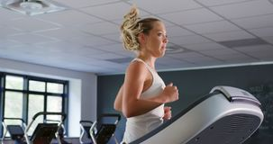 Runner on treadmill. Side view of a young Caucasian woman running on a treadmill stock video