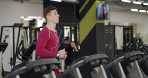 Runner at the Treadmill. Tired jogger man in headphones running on a treadmill in the gym stock video footage