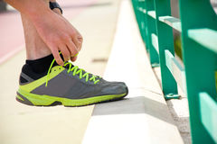 Runner tying his running shoes. On running track Royalty Free Stock Photo