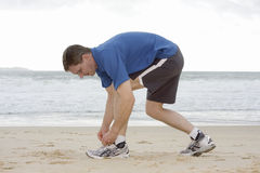Runner tying his shoes. Runner tyine his shoes on a beach Stock Photography
