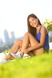 Runner tying running shoes. Woman jogging during outdoor workout in city park. Beautiful young mixed race athlete working out in Montreal, Quebec, Canada royalty free stock photos