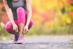 Free Runner Tying Running Shoes Laces In Autumn Background. Athlete Woman Getting Ready To Run Race In Fall Landscape With Yellow Royalty Free Stock Images - 156885529