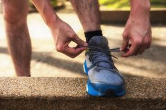 Runner tying running shoes with sunset light. Male Runner tying running shoes or shoelace on footpath with sunset light and getting ready for run. Healthy Stock Images
