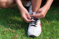 Runner tying running shoes. Woman jogging Royalty Free Stock Images