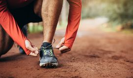 Runner tying shoe laces. Close up shot of an athlete tying his shoe laces. Man tightening his shoe laces resting on one knee on a mud track Royalty Free Stock Images