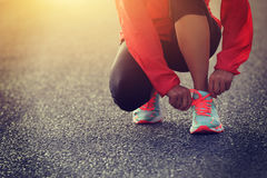 Runner tying shoelace on country road royalty free stock image