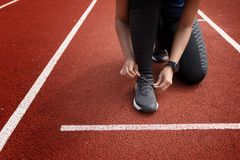 Runner tying shoelaces on run tracks lanes. In stadium ready for race competition stock photography
