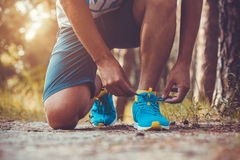 Runner tying shoelaces on sneakers. Morning jogging in the forest Stock Photography