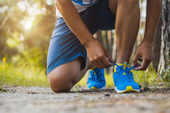 Runner tying shoelaces on sneakers. Morning jogging in the forest Royalty Free Stock Photography