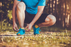 Runner tying shoelaces on sneakers. Morning jogging in the forest Royalty Free Stock Photo