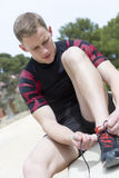 Runner tying the shoelaces. Young male runner is tying the shoelaces of the sneaker before starting a running session outdoors - focus on the left eye Royalty Free Stock Images