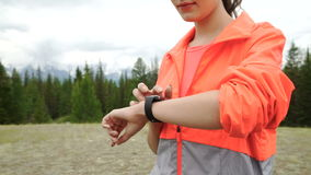 Runner using smartwatch fitness tracker and heart rate monitor watch jogging on trail in forest. Female athlete checking stock footage