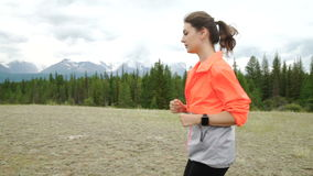 Runner using smartwatch fitness tracker and heart rate monitor watch jogging on trail in forest. Female athlete checking stock video footage