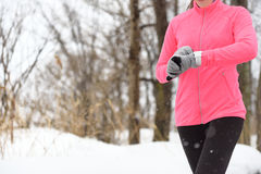 Runner using smartwatch jogging running in winter stock images