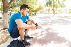 Runner Using Smartwatch And Phone While Sitting In Park. Male runner using smartwatch and phone while sitting in park on sunny day Royalty Free Stock Photography