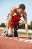 Runner Waiting With Baton At Starting Block. Male runner waiting at the starting block with a baton on racing track Stock Photo