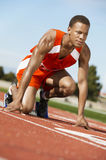 Runner Waiting At Starting Block. Male runner waiting at the starting block on race track Royalty Free Stock Images