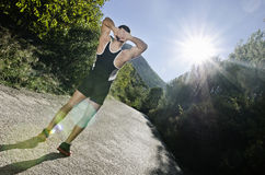 Runner warming arms with sun flare. Runner man warming arms with sun light flare effect in outdoors, warm up and stretching Stock Photo