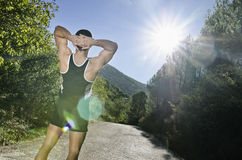 Runner warming legs with sun flare. Runner man warming arms with sun light flare effect in outdoors, warm up and stretching Stock Images