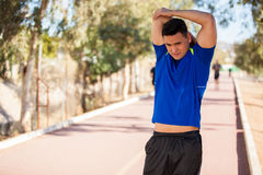 Runner warming up and stretching. Handsome young man stretching and warming up at a running track on a sunny day Royalty Free Stock Photography