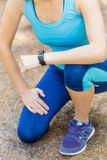 Runner woman arms with heart rate monitor and legs in forest tra Royalty Free Stock Image