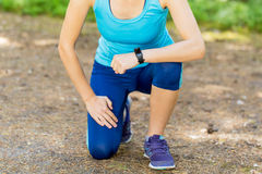 Runner woman arms with heart rate monitor and legs in forest tra Stock Photo
