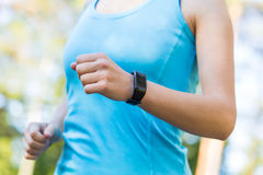 Runner woman arms with heart rate monitor for running in forest. Stock Image