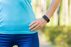 Runner woman arms with heart rate monitor for running in forest. Royalty Free Stock Image