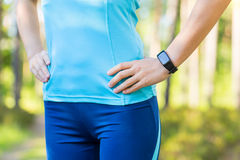Runner woman arms with heart rate monitor for running in forest. Royalty Free Stock Photo