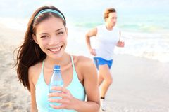 Runner woman drinking Stock Images